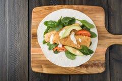 Burrito esmigalhado da faixa de peixes com abacate e tomate foto de stock