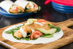 Burrito esmigalhado da faixa de peixes com abacate e tomate imagens de stock
