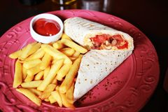 Burrito with French fries and ketchup on the red plate and napki. N. Tasty burrito Royalty Free Stock Photo