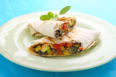 Burrito with grilled vegetables. And sauce with cheese royalty free stock image