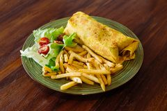 Burrito mexican cuisine wrap with french fries. On wooden table Royalty Free Stock Photography