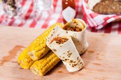 Burrito mit Mais auf hölzernem Brett lizenzfreie stockbilder
