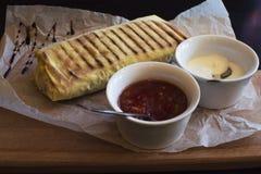 Burrito no papel com salsa imagens de stock royalty free