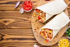 Burrito in tartilla with meat, vegetables, white beans, red pepper, corn. Delicious lunch, Mexican food, homemade snack. Burrito in tartilla with meat stock images
