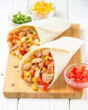 Burrito in tartilla with meat, vegetables, white beans, red pepper, corn. Delicious lunch, Mexican food, homemade snack. Burrito in tartilla with meat royalty free stock photography