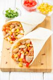 Burrito in tartilla with meat, vegetables, white beans, red pepper, corn. Delicious lunch, Mexican food, homemade snack. Burrito in tartilla with meat stock photos