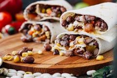Burrito vegetariano agradable sobre la tabla negra en el tablero de madera fotos de archivo