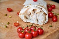 Burrito vegetariano con le verdure decorate con i pomodori ciliegia tagliati vicino su Sui piccoli pomodori ciliegia vaghi della  Fotografia Stock