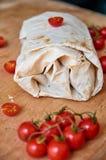 Burrito vegetariano con le verdure decorate con i semi del cardamomo su fondo di legno marrone Sui pomodori ciliegia vaghi della  Immagini Stock Libere da Diritti