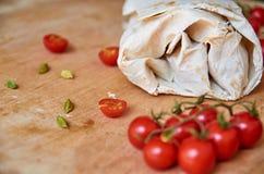 Burrito vegetariano con le verdure decorate con i semi del cardamomo su fondo di legno marrone Sui pomodori ciliegia vaghi della  Fotografia Stock Libera da Diritti