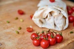 Burrito vegetariano con le verdure su fondo vago Sui piccoli pomodori ciliegia della priorità alta sulla fine di legno marrone de Immagine Stock Libera da Diritti