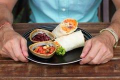 Burritoen på keramik, mannen äter en burrito som är smaklig, det är användbar vegetarisk mat arkivbilder