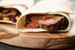Burritos with beef steak, corn, black beans and salsa sauce on cutting board Stock Image