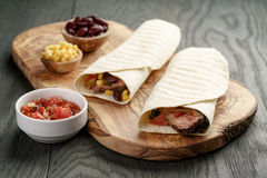 Burritos with beef steak, corn, black beans and salsa sauce on cutting board Stock Photography