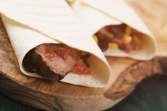 Burritos with beef steak, corn, black beans and salsa sauce on wood table Royalty Free Stock Image