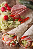 Burritos with ham, cheese and fresh vegetables close-up. vertica. Burritos with ham, cheese and fresh vegetables close-up on the table. vertical Royalty Free Stock Image