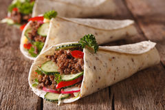 Burritos with minced meat and fresh vegetables close-up. Horizon. Burritos with minced meat and fresh vegetables close-up on the table. Horizontal Stock Photo