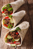 Burritos with minced meat and fresh vegetables close-up. vertica. Burritos with minced meat and fresh vegetables close-up on the table. vertical Stock Photos