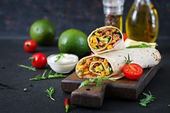 Burritos wraps with beef and vegetables on black background. Beef burrito, mexican food stock photo