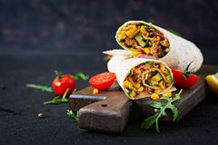 Burritos wraps with beef and vegetables on black background. Beef burrito, mexican food stock images