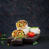 Burritos wraps with beef and vegetables on black background. Burritos wraps with beef and vegetables on  black background. Beef burrito, mexican food Stock Photos