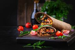 Burritos wraps with beef and vegetables on dark wooden background. Burritos wraps with beef and vegetables on  dark wooden background. Beef burrito, mexican