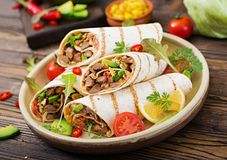 Burritos wraps with beef and vegetables on a wooden background. Beef burrito , mexican food. Royalty Free Stock Photos