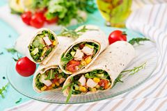 Burritos wraps with chicken and vegetables on light background. Burritos wraps with chicken and vegetables on light  background. Chicken burrito, mexican food Stock Images