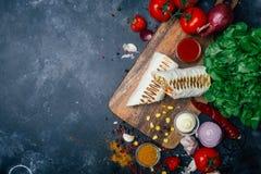 Burritosomslagen met geroosterde vlees en groenten - peper, tomaten en graan stock afbeelding