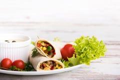 Burritosomslagen met groenten op houten achtergrond stock foto's