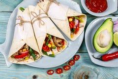 Burritossjalar med höna och grönsaker på ljus bakgrund Feg burrito, mexikansk mat Mat på gatan Skjutit i en studio arkivfoto