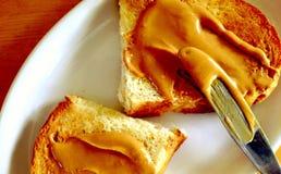 Burro di arachide naturale di diffusione su pane tostato Immagine Stock Libera da Diritti