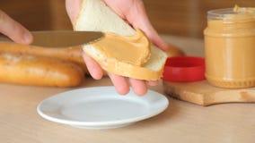 Burro di arachidi cremoso saporito che è sparso sul pane tostato bianco video d archivio