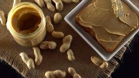 Burro di arachidi saporito che è sparso sul pane tostato bianco archivi video