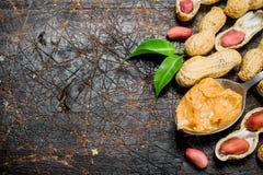 Burro di arachidi in un cucchiaio con le foglie fotografie stock
