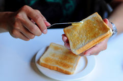 Burro di diffusione su pane tostato Fotografia Stock