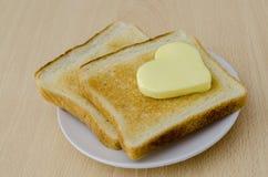 Burro a forma di del cuore su pane tostato Fotografie Stock Libere da Diritti