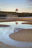 Burry Port Lighthouse at twilight. Taken in vertical format with the lighthouse reflecting in a puddle in the sandy beach Royalty Free Stock Image