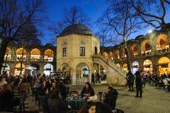 BURSA, TURKEY- JANUARY 24, 2015: Tea garden and silk shops in Koza Han Silk Bazaar. Koza Han is very old, built in 1451. There are. Little shops that sell silk royalty free stock photos