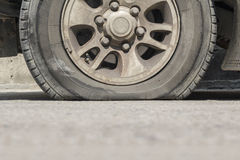 Burst car tire on street. Royalty Free Stock Images