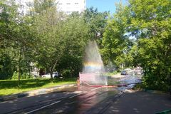 Burst pipe. The incident in the city. The work of public services. From the leaky hose gushing water into the sky. Rainbow in the. Air royalty free stock image