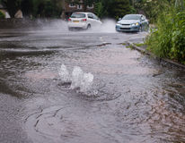 Burst water main. Cars driving through flooded road caused by burst water main royalty free stock photography