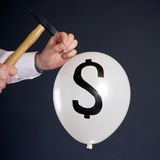 Bursting The Financial Bubble. Businessman hitting a nail into a white balloon with a dollar symbol Stock Photos