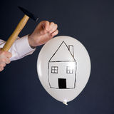 Bursting The Real Estate Bubble. Businessman hitting a nail into a white balloon with a house Stock Image