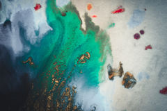Bursts of multicolored paint. S and mixed together white paper. Drawn splashes of paints of different colors on white surface. Blue, yellow, red, green color Royalty Free Stock Images
