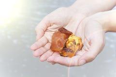Bursztyn w ręce z jaskrawym odbiciem na palmie przeciw tłu morze Fotografia Stock