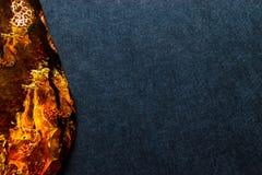 Bursztynu kamień na zmroku - błękitna tło powierzchnia Z Bezpłatną przestrzenią obraz stock