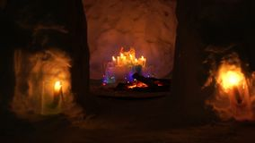 Christmas installation inside of snow house with colorful icy plafonds and burning candles