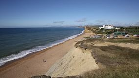 Burton Bradstock beach West Dorset England uk with people enjoying a beautiful day with blue sky and sea stock footage