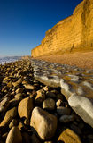 Burton Bradstock, Dorset, UK. Winter sun and low tide at Burton Bradstock, Dorset, UK highlighting the golden sandstone cliffs and rock ledges. The jurassic Stock Image